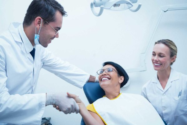 Male dentist shaking hands with female patient in chair. Dental hygienist by their sides, everyone is smiling.