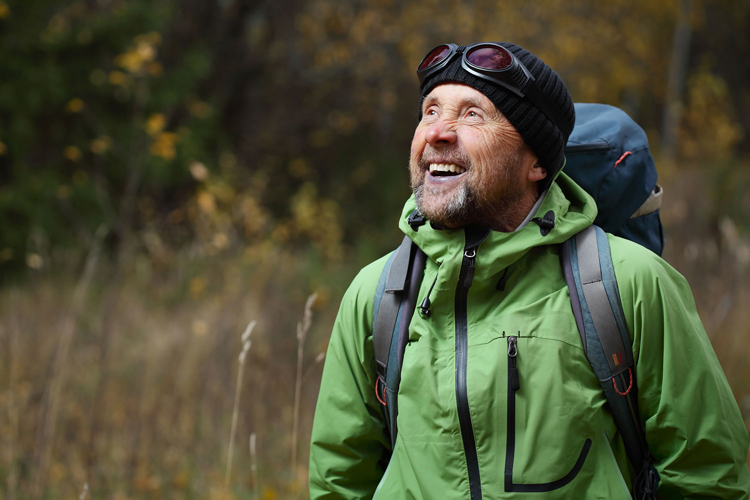 An older man in a green jacket and hiking gear, looking up and smiling with trees and a field in the background