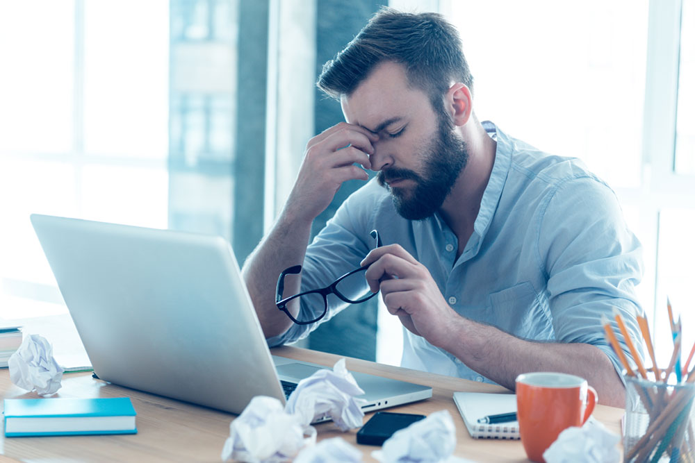 man stressed out at work with a headache